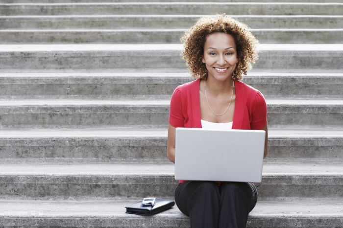 Portrait of a smiling young African American woman using laptop